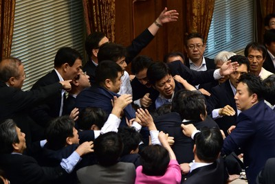 Japanese ruling and opposition lawmakers scuffle at the Upper House's ad hoc committee session for the controversial security bills at the National Diet in Tokyo on Sept. 17, 2015. (AFP PHOTO/Yoshikazu Tsuno)