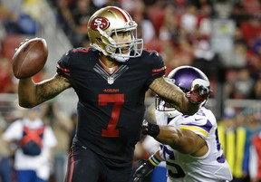 San Francisco 49ers quarterback Colin Kaepernick rolls out to pass as Minnesota Vikings outside linebacker Anthony Barr applies pressure during the second half of an NFL football game in Santa Clara, Calif., on Sept. 14, 2015. (AP Photo/Marcio Jose Sanchez)