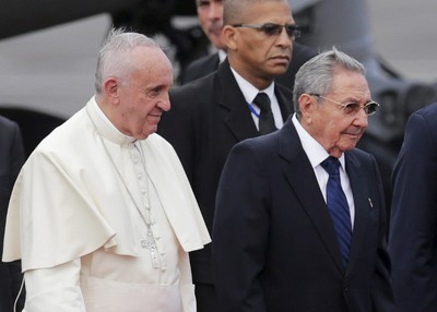 Pope Francis (L) is escorted by Cuba's President Raul Castro during his arrival at the airport in Havana September 19, 2015. Pope Francis begins a nine-day tour of Cuba and the United States on Saturday where he will see both the benefits and complexities of a fast-evolving detente between the old Cold War foes that he helped broker. Better sensitized to the issue than predecessors because of his Latin American roots, the 78-year-old Argentine pontiff facilitated a back channel for talks and sent missives to Presidents Castro and Barack Obama in 2014. REUTERS/Claudia Daut