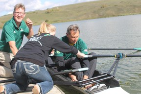 Rustlers rowing coach Peter Walsh and a team member help Vermilion-Lloydminster MLA Richard Starke into a canoe at the Vermilion Provincial Park on Thursday.