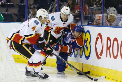 Edmonton Oilers' Taylor Hall (4) is checked byt Calgary Flames' Markus Granlund (60) and Kris Russell (4) during the first period of a pre-season NHL game at Rexall Place in Edmonton, Alta. on Monday September 21, 2015. Ian Kucerak/Edmonton Sun/Postmedia Network