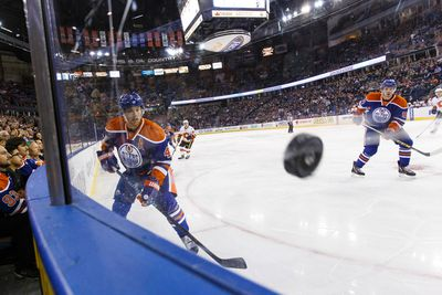 Edmonton Oilers' Taylor Hall (left) banks the puck off the game while Connor McDavid (right) watches during the first period of a pre-season NHL game versus the Calgary Flames at Rexall Place in Edmonton, Alta. on Monday September 21, 2015. Ian Kucerak/Edmonton Sun/Postmedia Network