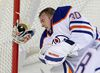 Goalie Ben Scrivens from the Edmonton Oilers makes a save with his face as he took a shot off his mask, knocking it off in the process as he and his team took on the Calgary Flames in pre-season NHL hockey action at the Scotiabank Saddledome in downtown Calgary, Alta. on Monday September 21, 2015. Stuart Dryden/Calgary Sun/Postmedia Network