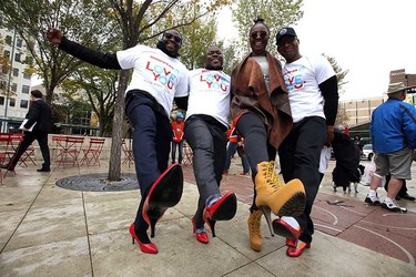 Team Shoppers Drung Mart Kodjo Boateng, Lekan Oladokun, Morenike Olaosebikan, and Karlito Mitchell keck up their heels during Walk a Mile in Her Shoes event at Churchill Square in Edmonton, Alta., on September 21, 2015. Perry Mah/Edmonton Sun/Postmedia