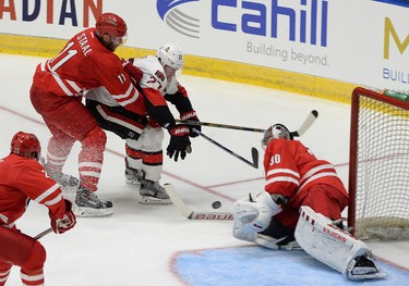 Caroline Hurricanes Jordan Staal (11) ties up Ottawa Senators Curtis Lazar(27) as he moves in on Hurricane's goalier Cam Ward during an NHL exhibition game in St. John's, N.L, Sunday, Sept.27, 2015. THE CANADIAN PRESS/Keith Gosse