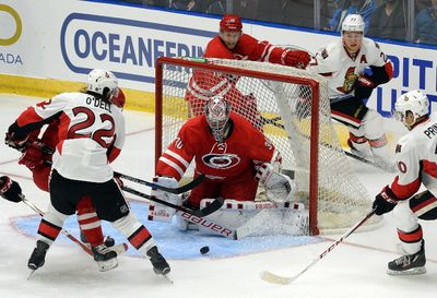 Caroline Hurricanes' goaltender Cam Ward, centre, watches a bouncing puck as players for both teams fight for position during an NHL exhibition game in St. John's, N.L, Sunday, Sept.27, 2015. THE CANADIAN PRESS/Keith Gosse