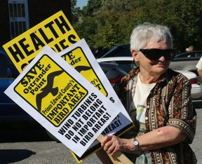 BRUCE BELL/THE INTELLIGENCER Prince Edward County Field Naturalists president Myrna Woods was well armed for the anti-wind development rally held by the Alliance to Protect Prince Edward County at the Milford Fairgrounds on Sunday.