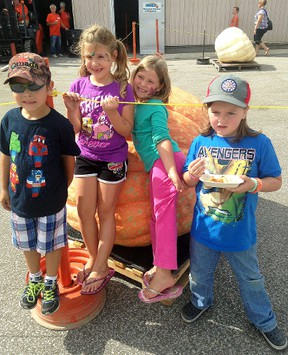 Joey Delima, far left, Kayla Delima, Deliah Parkes and Camry Mahoney post beside a large pumpkin at the Wallaceburg Kinsmen Pumpkinfest held at the Wallaceburg Kinsmen Community Centre on Saturday.