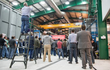 A worker gets a high vantage point to take a photograph of Liberal leader Justin Trudeau as he tours an electric transformer manufacturer Tuesday, September 29, 2015 in Winnipeg. THE CANADIAN PRESS/Paul Chiasson
