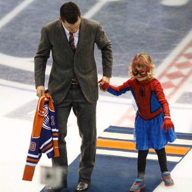 Edmonton captain Andrew Ference holds SpiderMable's, six-year-old cancer patient Mable Tooke, hand after she dropped the ceremonial puck before the start of an NHL game between the Edmonton Oilers and the Arizona Coyotes at Rexall Place in Edmonton, Alta. on Tuesday September 29, 2015. Ian Kucerak/Edmonton Sun/Postmedia Network