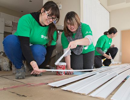 ACIC/Methapharm employees Annette Baluk (left), Aleea Fisher and Carrie Palermo paint baseboards on Friday at the Habitat for Humanity build on Aberdeen Avenue. (Brian Thompson/The Expositor)