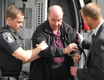 A handcuffed Brian Lucy is led from a police van to Brockville jail after being sentenced to five years in prison for indecent assault and gross indecency on Friday, October 2, 2015 in Brockvile, Ont. (Wayne Lowrie/Postmedia Network)