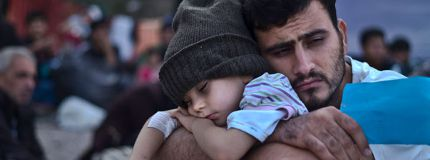A Syrian refugee child sleeps on his father's arms