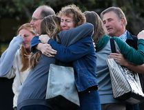 Faculty members embrace as they are allowed to return to Umpqua Community College Monday, Oct. 5, 2015, in Roseburg, Ore. The campus reopened to faculty for the first time since Oct. 1, when an armed suspect killed multiple people and wounded several others before taking his own life at Snyder Hall. (AP Photo/John Locher)