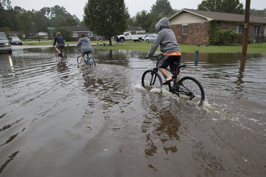 Children ride their bikes through flood waters on Rosewood Drive in Myrtle Beach, South Carolina October 5, 2015. Torrential rainfall that South Carolina's governor called a once-in-a-millennium downpour triggered flooding in the southeastern U.S. state on Sunday, causing at least eight deaths in the Carolinas. REUTERS/Randall Hill