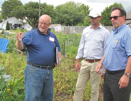 Derwyn Armstrong, co-ordinator of Chatham-Kent's community gardens, left, guides Communities in Bloom judges Alain Capelle and Richard Daigneault through the CLAC community garden in Chatham. File photo/ Postmedia Network