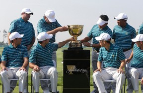 International team players touch the trophy as they attend a photo session for the Presidents Cup golf tournament at Jack Nicklaus Golf Club Korea in Incheon, South Korea, on Tuesday, Oct. 6, 2015. (Ahn Young-joon/AP Photo)