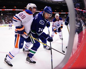 Brandon Davidson battles Canucks' Adam Cracknell in the corner during Saturday's game in Vancouver. (The Canadian Press)