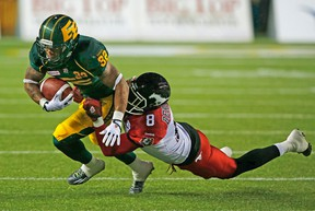 Edmonton Eskimos Kendial Lawrence (32) is brought down by Calgary Stampeders Fred Bennett (8) during their game at Commonwealth Stadium in Edmonton, Alberta on Saturday, September 12, 2015 PERRY NELSON - EDMONTON SUN / QMI AGENCY