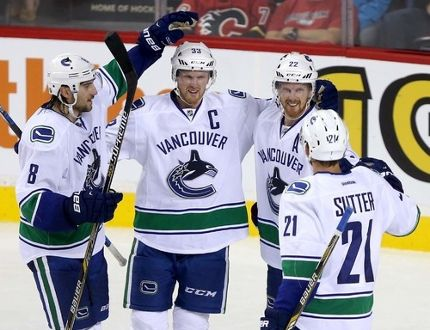 The Canucks celebrate Henrik Sedin's third-period goal in Wednesday's season-opening 5-1 win over the Calgary Flames. POSTMEDIA NETWORK