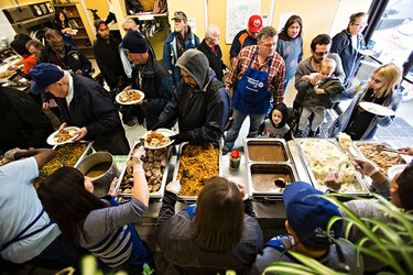 People line up during the 23rd annual Thanksgiving dinner at Millbourne Laundromat in Edmonton, Alta. on Monday, Oct. 12, 2015. Codie McLachlan/Edmonton Sun/Postmedia Network