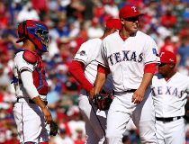 Derek Holland #45 of the Texas Rangers is taken out of the game in the third inning against the Toronto Blue Jays in game four of the American League Division Series at Globe Life Park in Arlington on October 12, 2015 in Arlington, Texas.   Ronald Martine