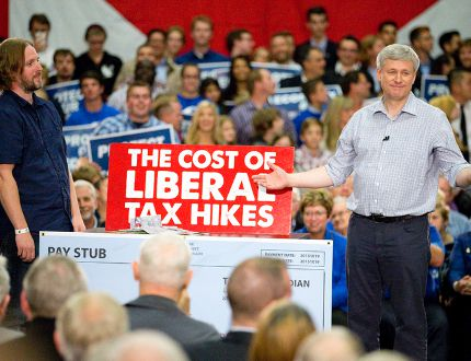 Tory leader Stephen Harper doles out cash, meant to signify the tax costs to a family under the leadership of a Liberal government, during a campaign stop Tuesday in London. (CRAIG GLOVER, The London Free Press)