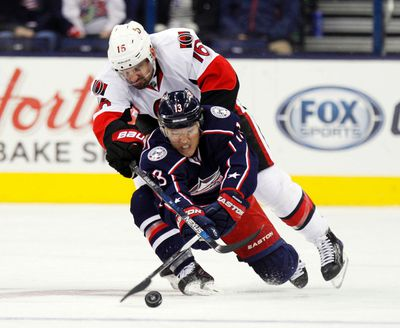 Ottawa Senators' Clarke MacArthur, top, works for the puck against Columbus Blue Jackets' Cam Atkinson during the second period of an NHL hockey game in Columbus, Ohio, Wednesday, Oct. 14, 2015. (AP Photo/Paul Vernon)