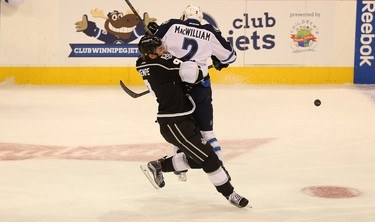 Manitoba Moose defenceman Andrew MacWilliam throws a shoulder into Ontario Reign forward Adrian Kempe at MTS Centre in Winnipeg on Thu., Oct. 15, 2015. Kevin King/Winnipeg Sun/Postmedia Network