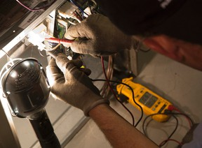 Roy Inch and Sons service technician Craig Hern uses a meter to measure the power running through a switch while conducting annual maintenance on a furnace in a Village Green Avenue home in London, Ont. on Tuesday September 8, 2015. Craig Glover/The London Free Press/Postmedia Network