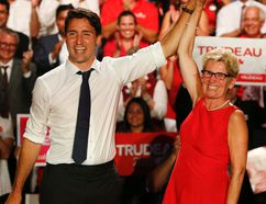 Federal Liberal leader Justin Trudeau, left, has his hand held aloft by Ontario Premier Kathleen Wynne at a Liberal rally held at the Daniels Spectrum in Toronto on August 17, 2015. (Jack Boland/Toronto Sun/Postmedia Network)