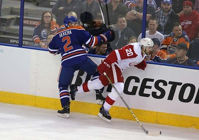 Edmonton Oilers' Andrej Sekera (2) checks  Detroit Red Wings' Drew Miller (20) during first period NHL action at Rexall Place in Edmonton, Alberta on October 21, 2015. Perry Mah/Edmonton Sun/Postmedia Network
