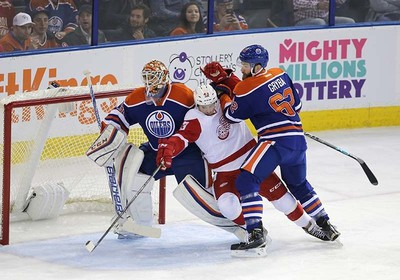Edmonton Oilers' Eric Gryba (62) checks  Detroit Red Wings' Darren Helm (43) to to ice in from of goaltender goalie Cam Talbot (33) during first period NHL action at Rexall Place in Edmonton, Alberta on October 21, 2015. Perry Mah/Edmonton Sun/Postmedia Network
