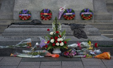 Flowers are placed on the Tomb of The Unknown Soldier following a ceremony marking the one year anniversary of the attack on Parliament Hill Thursday Oct. 22, 2015 at the National War Memorial in Ottawa. THE CANADIAN PRESS/Sean Kilpatrick