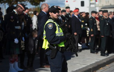 An armed Ottawa police officer keeps watch during a ceremony to unveil a memorial plaque to honour Corporal Nathan Cirillo on Thursday Oct. 22, 2015 at the National War Memorial in Ottawa. THE CANADIAN PRESS/Sean Kilpatrick