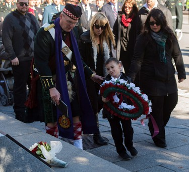Corporal Nathan Cirillo's son Marcus Cirillo places a wreath during a ceremony to unveil a memorial plaque on Thursday, Oct. 22, 2015 at the National War Memorial in Ottawa. to honour Corporal Nathan Cirillo. THE CANADIAN PRESS/Sean Kilpatrick