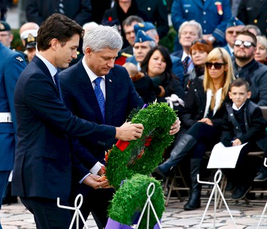 Prime Minister Stephen Harper and prime minister designate Justin Trudeau place a wreath during a ceremony marking the one year anniversary of the attack on Parliament hill Thursday Oct. 22, 2015 at the National War Memorial in Ottawa. . Errol McGihon/Ottawa Sun/Postmedia Network