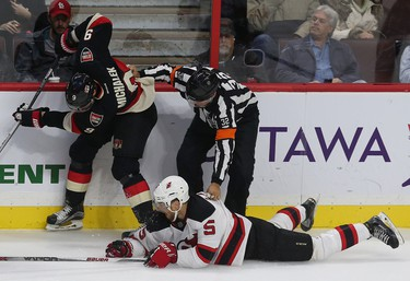 The Ottawa Senators took on the New Jersey Devils at Canadian Tire Centre in Ottawa Ontario Thursday Oct 22, 2015. Senators Milan Michalek and Devils Adam Larsson is held up by the referee during second period action Thursday.  Tony Caldwell/Ottawa Sun/Postmedia Network