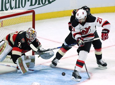 New Jersey Devils' Kyle Palmieri (21) battles for the puck with Ottawa Senators' Mark Borowiecki (74) as goaltender Andrew Hammond (30) watches for the puck during NHL hockey second period action in Ottawa Thursday October 22, 2015. THE CANADIAN PRESS/Fred Chartrand