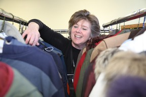 Jason Miller/The Intelligencer Salvation Army director, Abby Mills, sort through coats already donate for this year's Coats for Folks program. The program is less than halfway from the 250 to 300 coat donation marker.