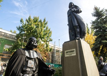 """A participant dressed as Darth Vader, a character from the """"Star Wars"""" film, takes part in an inauguration ceremony of a Darth Vader monument, formerly a statue of Soviet founder Lenin, in the southern Ukrainian city of Odessa on Oct. 23, 2015. (AFP PHOTO/VOLODYMYR SHUVAYEV)"""