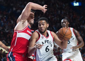 Toronto Raptors' Cory Joseph, right, drives to the basket as Washington Wizards' Kris Humphries defends during first quarter pre-season basketball action in Montreal on Oct. 23, 2015. (THE CANADIAN PRESS/Graham Hughes)