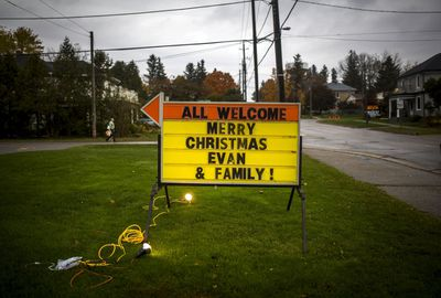"A person walks behind a sign wishing terminally-ill boy, Evan Leversage ""Merry Christmas"" in St. George, Ont., October 24, 2015. Evan Leversage, is a seven-year-old boy who has been living with inoperable brain cancer since he was two years old. His family has organized a Christmas celebration in early October complete with a full parade, in case Evan does not live to celebrate his last Christmas day on the traditional date of December 25. REUTERS/Mark Blinch"