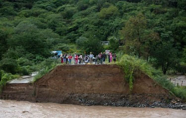People stand at the edge of a collapsed bridge, overlooking the Ameca River in Cofradia, some 200 km northwest of Guadalajara, Mexico, Saturday, Oct. 24, 2015. Hurricane Patricia made landfall Friday on a sparsely populated stretch of Mexico's Pacific coast as a Category 5 storm, avoiding direct hits on the resort city of Puerto Vallarta and major port city of Manzanillo as it weakened to tropical storm force while dumping torrential rains that authorities warned could cause deadly floods and mudslides. (AP Photo/Eduardo Verdugo)