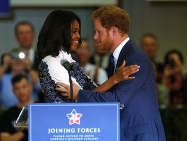 Britain's Prince Harry embraces U.S. first lady Michelle Obama while addressing servicemen and women at Fort Belvoir, Virginia October 28, 2015. REUTERS/Kevin Lamarque