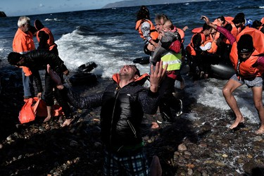 A man reacts as he arrives, with other refugees and migrants, on the Greek island of Lesbos, on October 28, 2015, after crossing the Aegean sea from Turkey. At least five migrants including three children, died on October 28, 2015 after four boats sank between Turkey and Greece, as rescue workers searched the sea for dozens more, the Greek coastguard said. The new accidents brought to 34 the number of migrants found dead in Greek waters this month, according to an AFP tally based on data from Greek port police. Since the start of the year, 560,000 migrants and refugees have arrived in Greece by sea, out of over 700,000 who have reached Europe via the Mediterranean, according to the International Office for Migration (IOM). AFP PHOTO / ARIS MESSINIS
