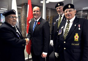 Royal Canadian Legion members Norm Pichie (left), Caspar Koevoets and Ross Seip present London Mayor Matt Brown with the first poppy of the 2015 Poppy Campaign in London Ont. October 27, 2015. CHRIS MONTANINI\LONDONER\POSTMEDIA NETWORK
