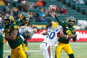 Edmonton's Mike Reilly (13) is tackled by Montreal's Henoc Muamba (50) during the first half of a CFL game between the Edmonton Eskimos and the Montreal Alouettes at Commonwealth Stadium in Edmonton, Alta.. on Sunday November 1, 2015. Ian Kucerak/Edmonton Sun/Postmedia Network