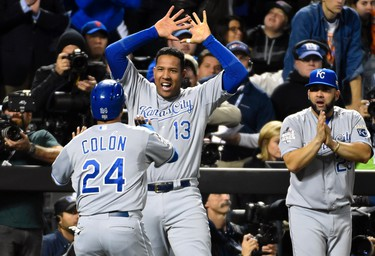 Nov 1, 2015; New York City, NY, USA; Kansas City Royals pinch hitter Christian Colon (24) is congratulated by teammates Salvador Perez (13) and Kendrys Morales (25) after scoring a run against the New York Mets in the 12th inning in game five of the World Series at Citi Field. Robert Deutsch-USA TODAY Sports