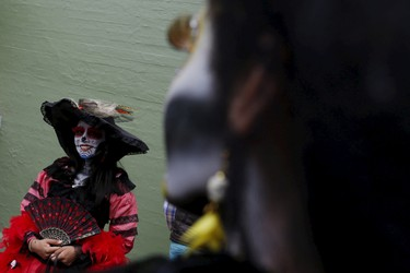 """A woman with her face painted to look like the popular Mexican figure called """"Catrina"""", looks on as she takes part in the annual Catrina Fest in Mexico City November 1, 2015. According to participants, about 310 women gathered at the Catrina Fest, where women dressed to look like """"Catrina"""", a character also known as """"The Elegant Death"""", created by Guadalupe Posada in the early 1900s. Mexicans celebrate the annual Day of the Dead on November 1 and 2. REUTERS/Carlos Jasso"""